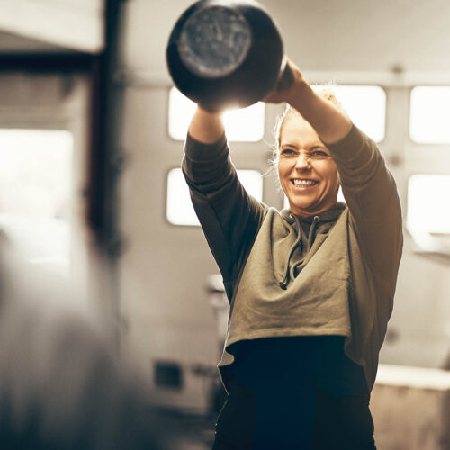 Fit young woman in sportswear smiling while swinging a dumbbell over her head during a workout session in a gym